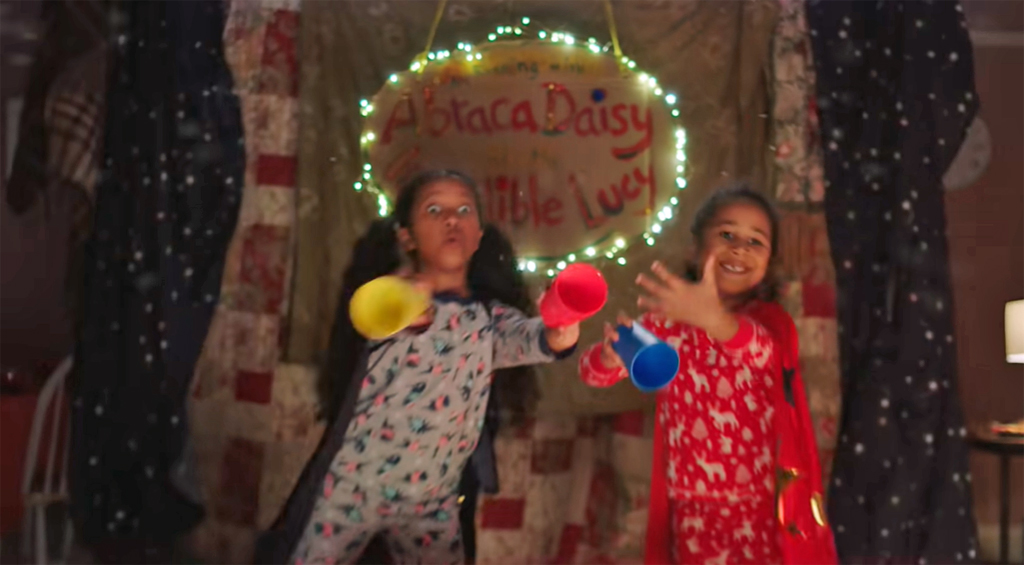image shows two young girls performing a magic trick on a homemade stage in their front room