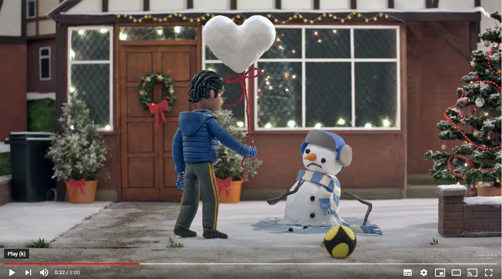 image shows an animated boy giving a heart-shaped balloon made out of snow to a collapsed snowman