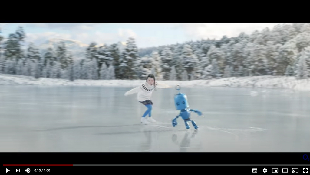 Image shows a young skater on an ice rink dancing with a blue robot